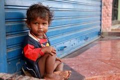 友好无家可归的女孩的看起来逗人喜爱和有连续鼻子,穿戴肮脏的衣裳坐街道 免版税库存图片