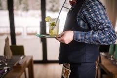 友好的侍者服务酒精mohito鸡尾酒、恰好装饰的刷新的石灰和薄菏鸡尾酒, 库存图片