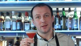 友好的侍酒者看照相机和邀请您到他的酒吧 库存图片