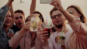 友好的公司享用可口鸡尾酒并且采取selfies 夏天都市鸡尾酒 股票录像