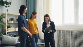 友好的地产商谈话与客户显示纸的男人和妇女在新房 影视素材