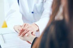 友好的女性医生` s递握鼓励和同情特写镜头的女性耐心` s手 合作,信任 免版税库存照片