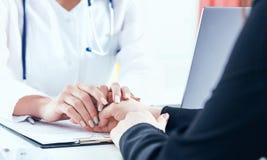友好的女性医生` s递握鼓励和同情特写镜头的女性耐心` s手 合作,信任 免版税库存图片