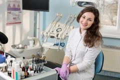 友好的女性牙医画象在牙齿办公室 医生佩带的白色制服,紫罗兰色手套 牙科 免版税库存照片