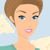友好的女性牙医展示绣花丝绒 免版税库存图片