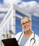 友好的女性白肤金发的医生或护士在大厦前面 免版税库存图片