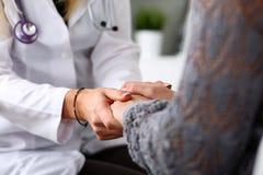 友好的女性医生举行耐心手在recept期间的办公室 免版税库存照片