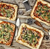 友好的宴餐在家 在一张木桌上的开胃自创薄饼 免版税库存照片