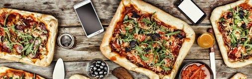友好的宴餐在家 在一张木桌上的开胃自创薄饼 免版税库存图片