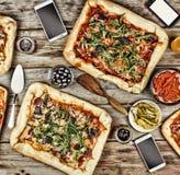 友好的宴餐在家 在一张木桌上的开胃自创薄饼 库存图片