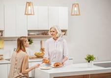 友好的家庭饮用的茶用小圆面包在厨房里 库存照片