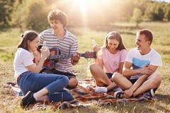 友好的年轻人水平的射击获得乐趣,一起花费时间在周末期间,坐地面,唱歌曲到吉他, 免版税库存照片