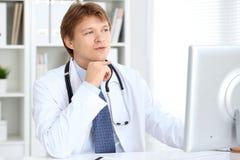 友好的男性医生坐在桌上并且在医院办公室工作 准备审查和帮助患者 图库摄影