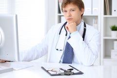 友好的男性医生坐在桌上并且在医院办公室工作 准备审查和帮助患者 库存图片