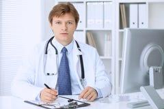 友好的男性医生坐在桌上并且在医院办公室工作 准备审查和帮助患者 免版税图库摄影