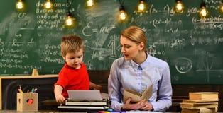 友好的老师和成人微笑的学生在教室,好老师寻求在网上答应了学生,数字式教育 免版税图库摄影