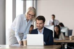 友好的辅导者训练雇员在帮助与计算机工作的办公室 库存图片