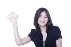 友好的青少年女孩挥动的你好或再见 免版税库存图片