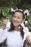 友好的滑稽的妇女用牛奶和母牛 免版税库存照片