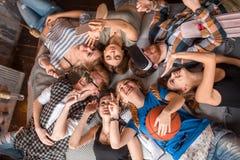 友谊、休闲、夏天和人概念-说谎在圈子的地板上的小组微笑的朋友户内 免版税图库摄影
