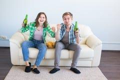 友谊、体育、娱乐和足球世界杯-有芯片和啤酒观看的体育的愉快的朋友在家 免版税图库摄影