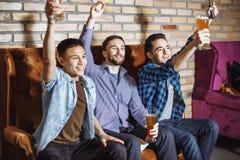 友谊、体育和娱乐概念-用啤酒在家看电视的愉快的男性朋友 免版税图库摄影