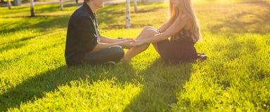 友谊和爱概念与一对年轻夫妇坐草和谈的特写镜头 免版税图库摄影