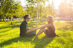 友谊和爱概念与一对年轻夫妇坐草和谈 库存图片