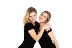 友谊和爱:两个微笑的女孩拥抱 免版税库存照片