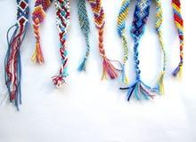 友谊镯子由与辫子的螺纹制成在白色背景 免版税库存照片