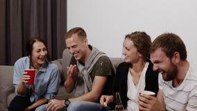 友谊,通信,集会谈话定期的快乐的白种人的朋友,获得乐趣,坐长沙发户内和 股票录像
