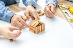 双人一位妇女建筑师画一个计划,在大纸片在办公桌和修造式样房子从木块酒吧 免版税库存照片
