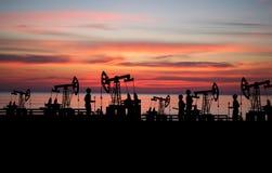 双人在有泵浦的油田 免版税库存照片
