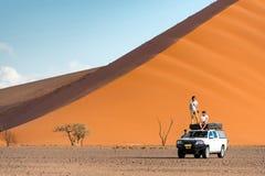 双人在露营车汽车在橙色沙丘附近 库存图片