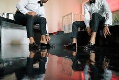 双人穿易穿脱的衣服黑光滑的鞋子,为婚礼做准备,黑色木地板-低角度 免版税库存照片