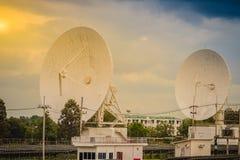 双大规模白色卫星盘在dramat下的太阳农场 免版税图库摄影