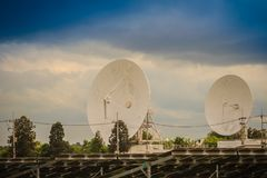 双大规模白色卫星盘在dramat下的太阳农场 免版税库存照片