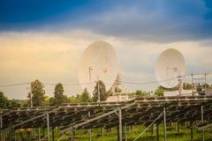 双大规模白色卫星盘在dramat下的太阳农场 免版税库存图片