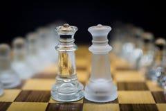 双女王/王后,在黑背景的冰冷的女王/王后棋子 免版税库存照片