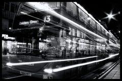 双层公共汽车在与轻的足迹的晚上牛津街 免版税库存图片