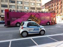 双层汽车通过一辆微型NYPD车,纽约的游览车驱动 库存图片