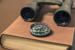 双筒望远镜、指南针和书 库存图片