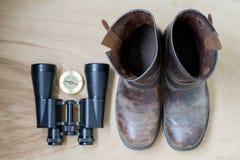 双筒望远镜、老起动和指南针, traveler& x27; s事,在木背景 免版税库存图片