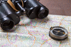 双筒望远镜和指南针在地图 库存图片