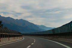 双线道机动车路有山背景 免版税库存图片