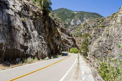 双线道路通过花岗岩岩石Canyon加利福尼亚国王的 图库摄影