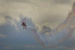 双翼飞机特技在灰色天空下 免版税库存图片