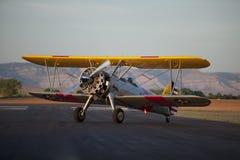 双翼飞机跑道坐的黄色 库存图片