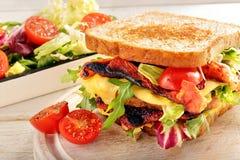 双重三明治用烟肉乳酪和菜在木backg 图库摄影