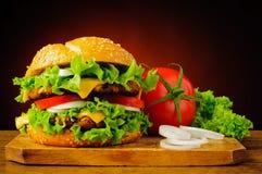 双重乳酪汉堡和新鲜蔬菜 免版税库存图片